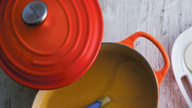 A red Le Creuset pot full of nourishing pumpkin soup